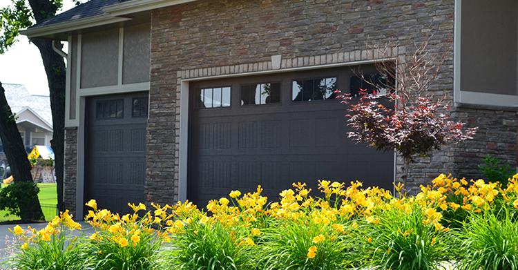 brick-home-dark-garage-doors-in-summer